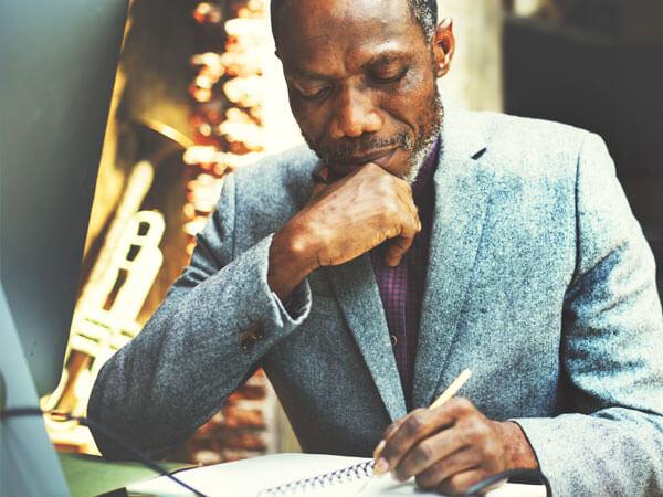 Мужчина вручную заполняет документ
