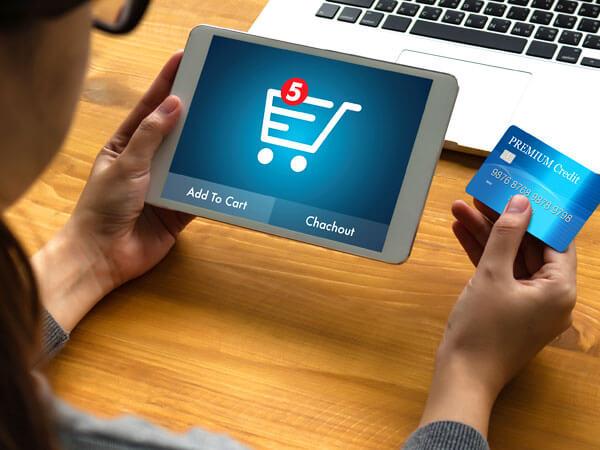 Человек делает покупки в интернет-магазине с помощью планшета