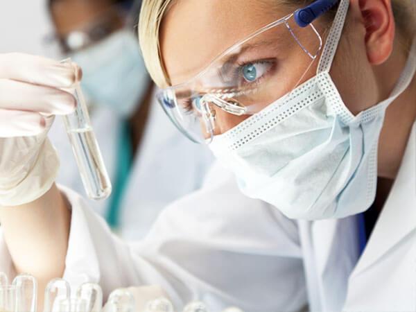 Исследователь смотрит на пробирку с жидкостью