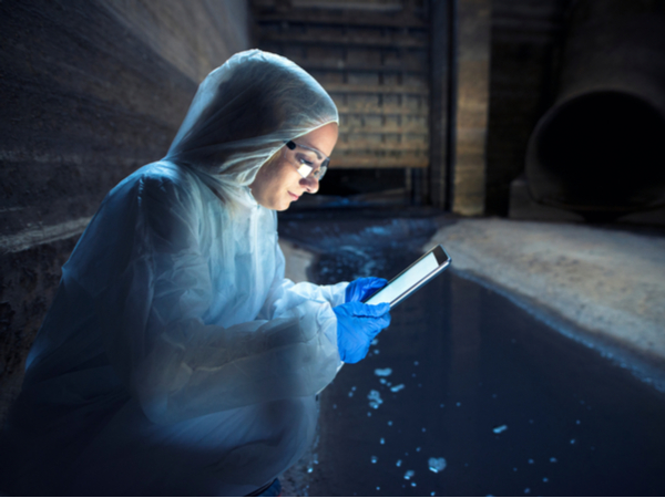 wastewater researcher looking at data on device